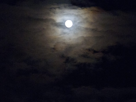 full moon glowing through clouds
